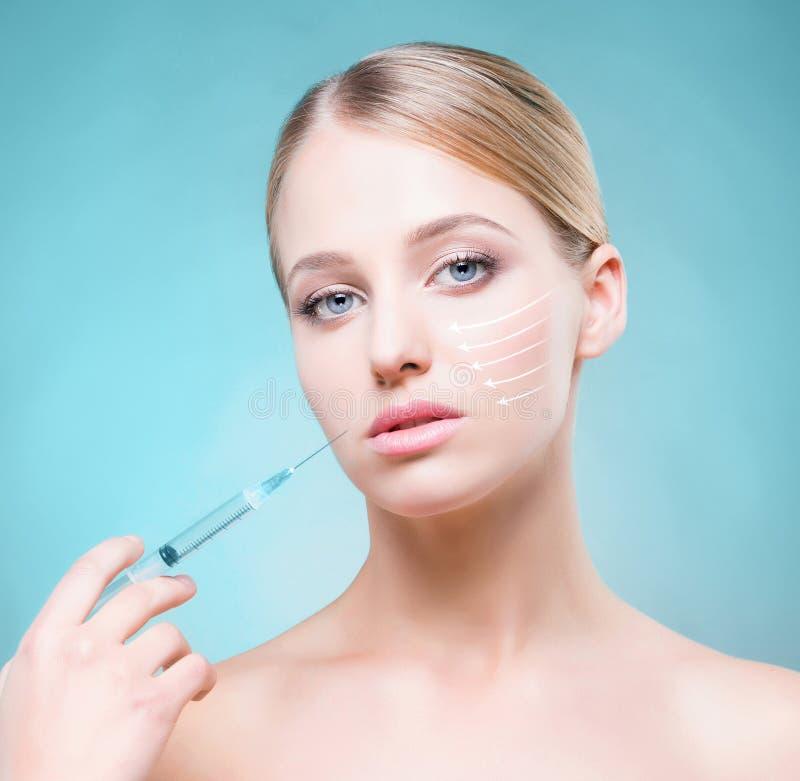 Młoda kobieta z strzykawki wstrzykiwania botox zdjęcia stock