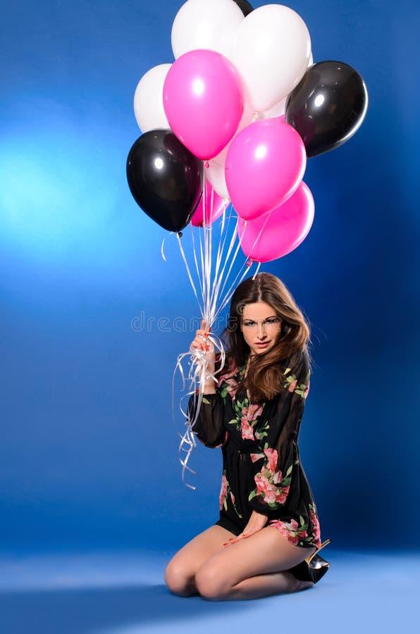 Młoda kobieta z stubarwnymi balonami obraz royalty free