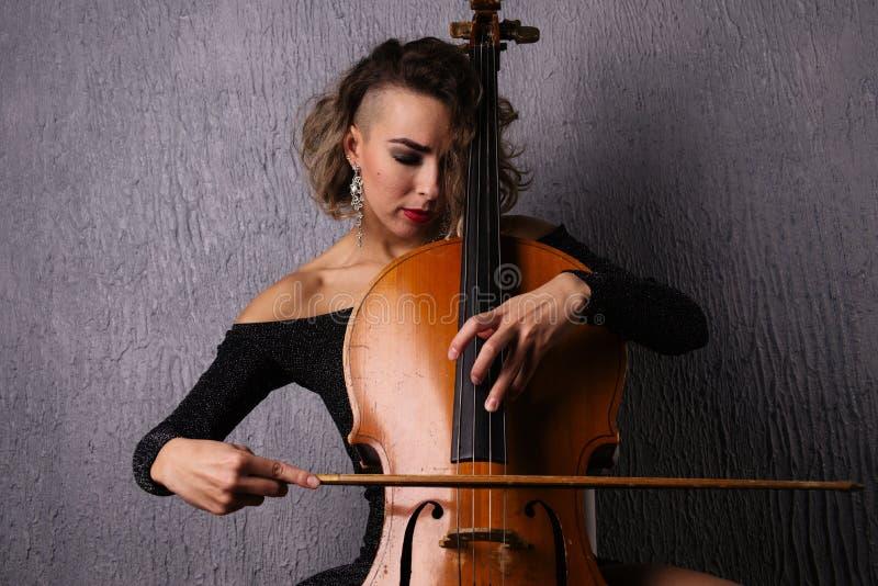 Młoda kobieta z trądzikiem bawić się wiolonczelę fotografia royalty free