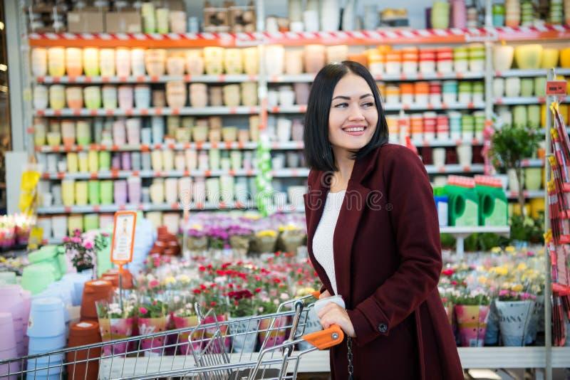 Młoda kobieta z wózek na zakupy kupienia kwiatami przy uprawia ogródek sklep fotografia stock