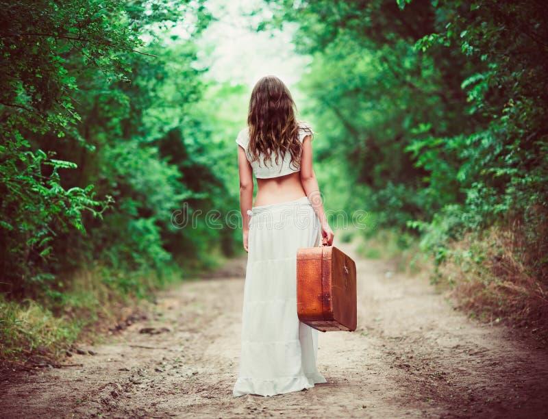 Młoda kobieta z walizką w ręce iść daleko od wiejską drogą obrazy stock