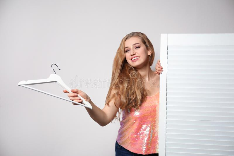Młoda kobieta z wieszakiem blisko falcowanie ekranu przeciw lekkiemu tłu obraz royalty free