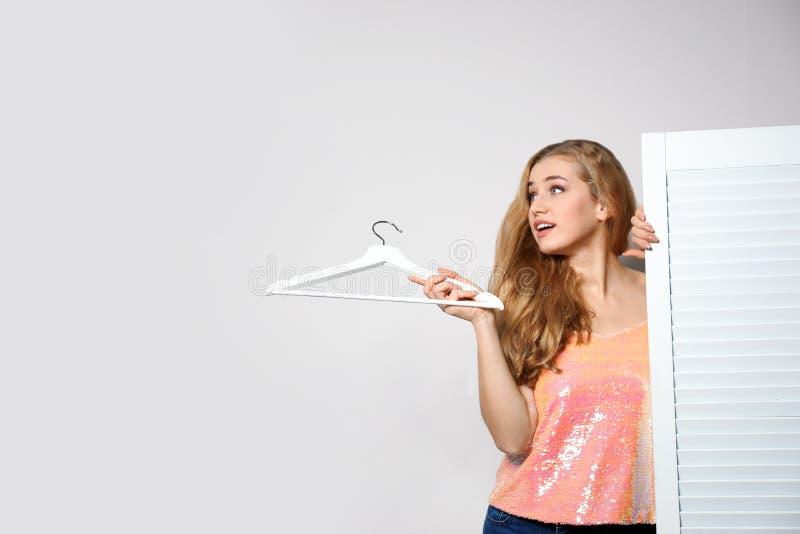 Młoda kobieta z wieszakiem blisko falcowanie ekranu przeciw lekkiemu tłu, przestrzeń dla teksta obraz stock