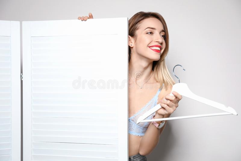 Młoda kobieta z wieszakiem za falcowanie ekranem przeciw lekkiemu tłu fotografia stock
