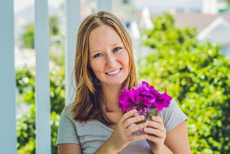 Młoda kobieta z wiosna purpurowymi kwiatami przeciw tła pojęcia kwiatu wiosna biały żółtym potomstwom fotografia stock