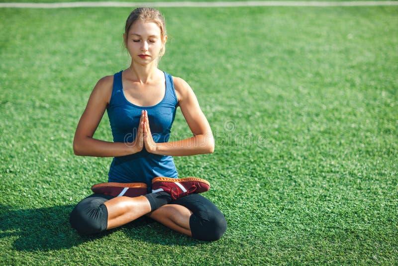 Młoda kobieta z zamkniętymi oczami w, joga na zielonej trawie w lecie na naturze i zdjęcia royalty free