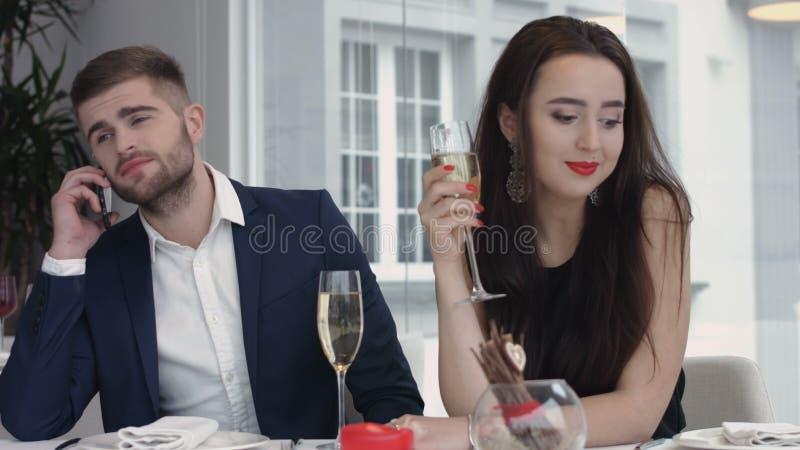 Młoda kobieta zanudzająca do teraz podczas gdy jej chłopak ma biznesową komórkę na telefonie komórkowym, obsługuje ruchliwie używ fotografia royalty free