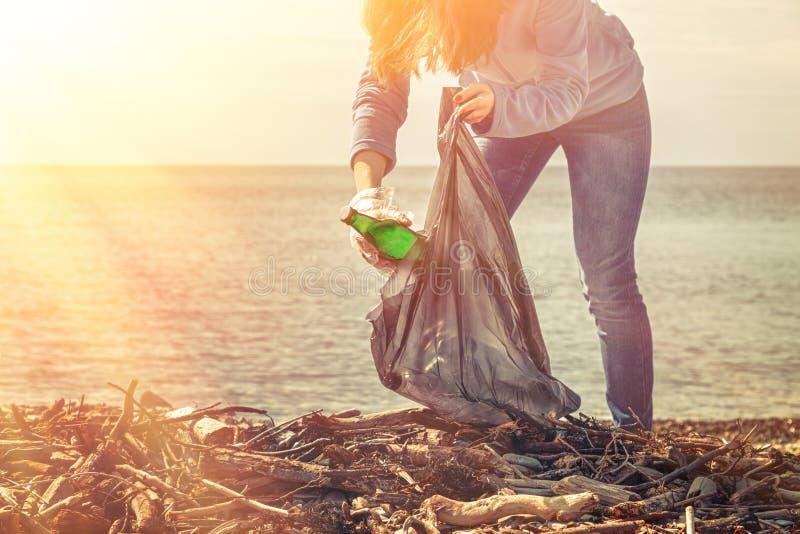 Młoda kobieta zgina puszek zbierać brudną szklaną butelkę Czyścić i ochrona środowiska Światło od prawego wierzchołka  zdjęcia royalty free