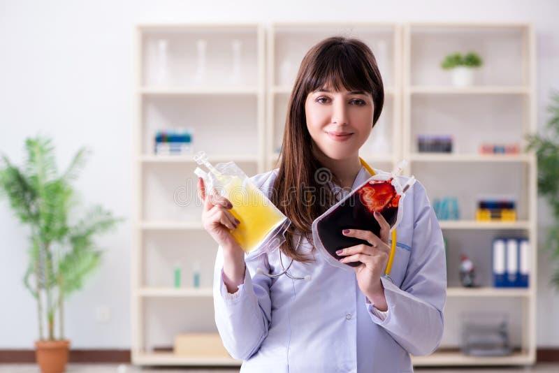 Młoda kobiety lekarka z torbą krwionośny osocze w szpitalu fotografia stock