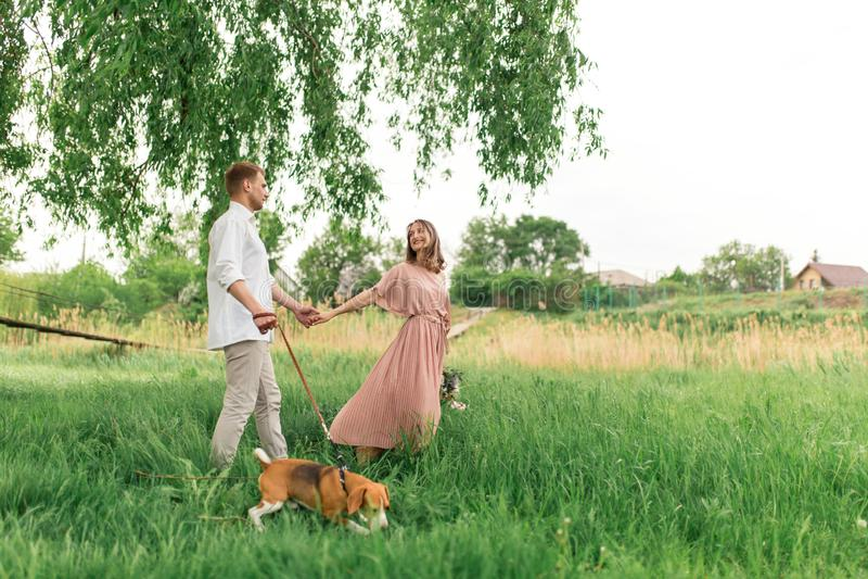 Młoda kochająca para ma zabawę i bieg na zielonej trawie na gazonie z ich ukochanym domowym psem hodujemy Beagle i a zdjęcia stock