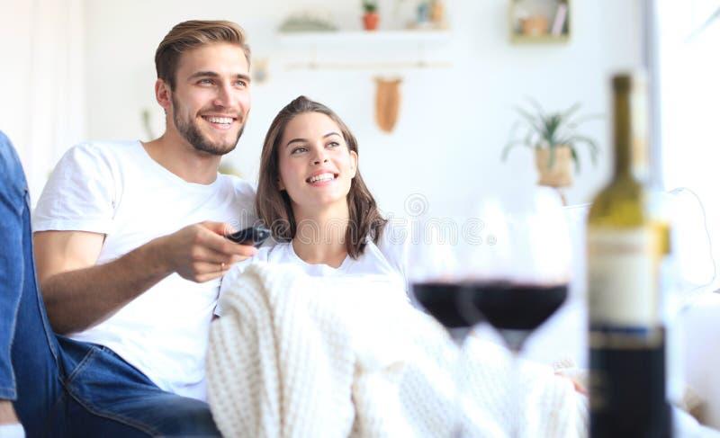 Młoda kochająca para ogląda tv i śmia się na kanapie w domu, pije szkło czerwone wino zdjęcia stock