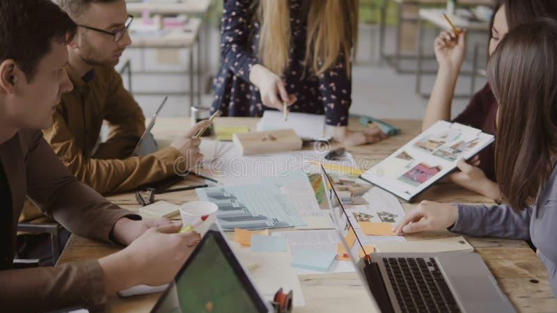 Młoda kreatywnie biznes drużyna w nowożytnym biurze Wieloetniczna grupa ludzi pracuje na architektonicznym projekcie wpólnie obrazy stock