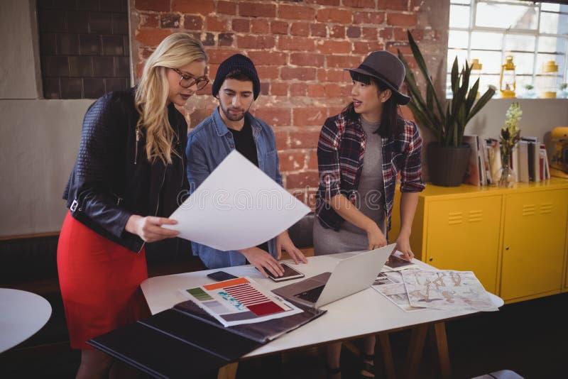Młoda kreatywnie drużyna dyskutuje nad papierami przy sklep z kawą zdjęcia stock