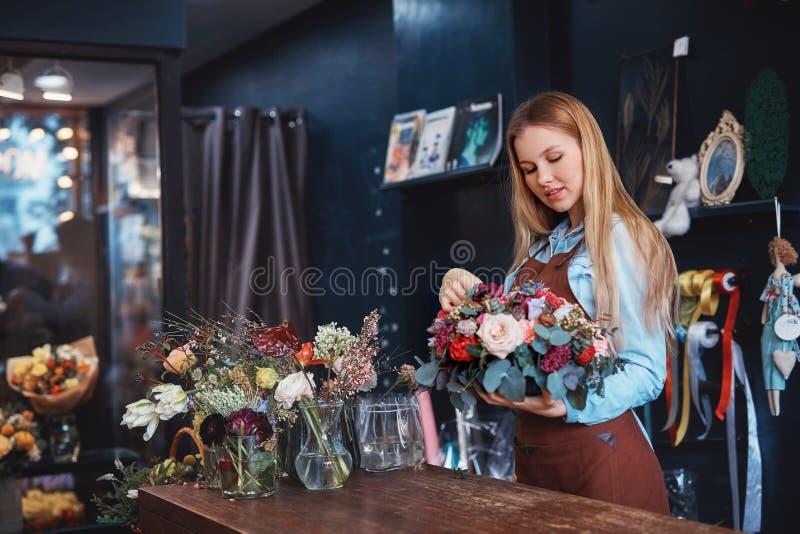 Młoda kwiaciarnia z kwiatami obrazy stock