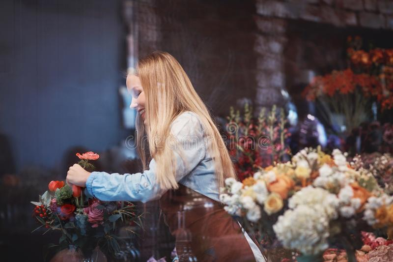 Młoda kwiaciarnia z kwiatami zdjęcia royalty free