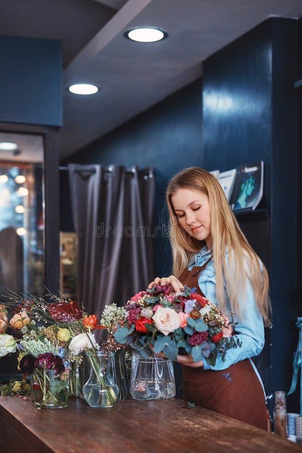 Młoda kwiaciarnia z kwiatami fotografia royalty free