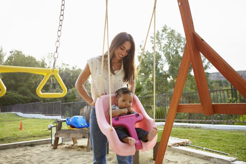 Młoda latynos matka pcha jej dziecka na huśtawce przy boiskiem w parku obraz royalty free