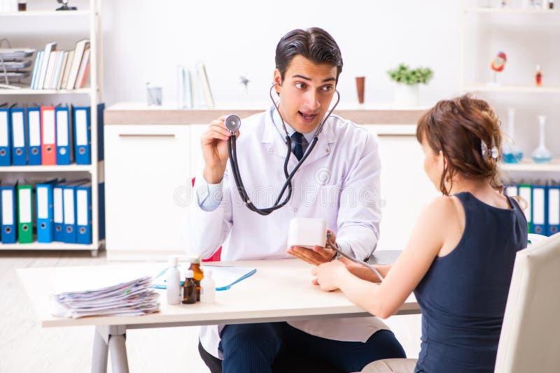 Młoda lekarka sprawdza kobiety ciśnienie krwi obrazy stock