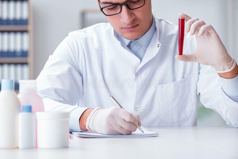 Młoda lekarka w lab z czerwoną tubką zdjęcie royalty free