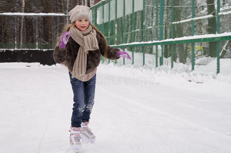 Młoda longhair dziewczyna jest ubranym przypadkową zimę odziewa na lodowym lodowisku fotografia stock