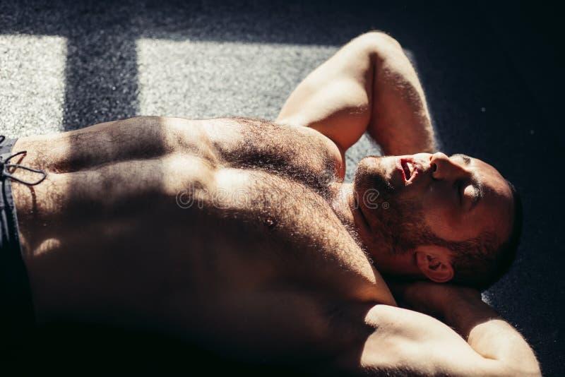 Młoda męska atleta na podłogowym robi situps w gym Sprawność fizyczna mężczyzna robi abs chrupnięciom obraz royalty free