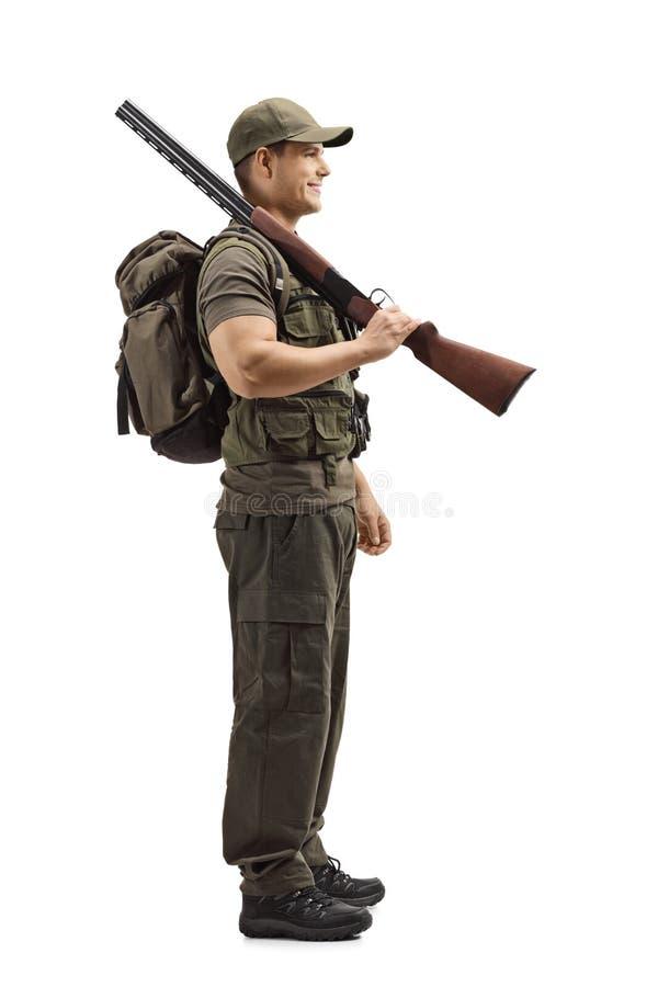 Młoda męska myśliwy pozycja z flintą na jego ramieniu zdjęcia royalty free