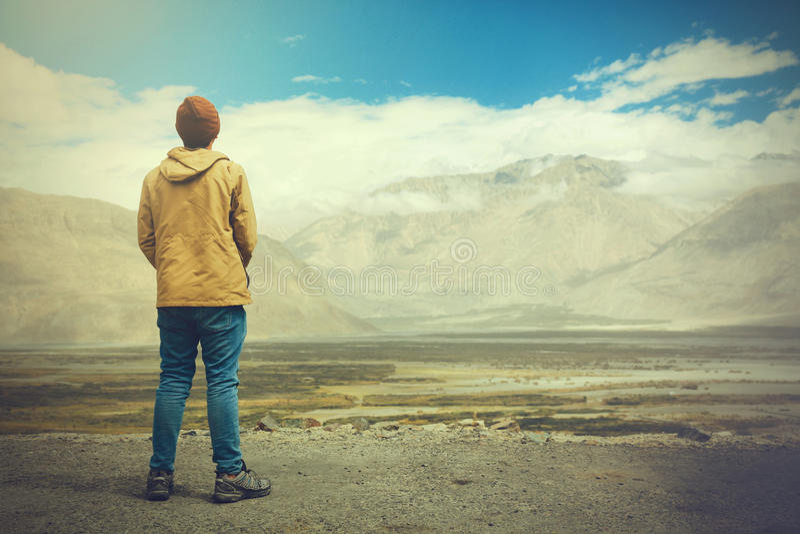 Młoda męska podróżnik pozycja na piasek falezie myśleć wokoło lub patrzeje naprzód coś w Leh, Ladakh, India fotografia royalty free