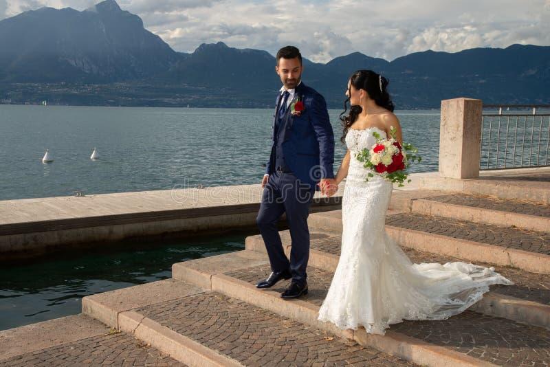 Młoda małżeńska para, przechadzająca się wzdłuż brzegu jeziora w Torri del Benaco, Włochy obraz royalty free