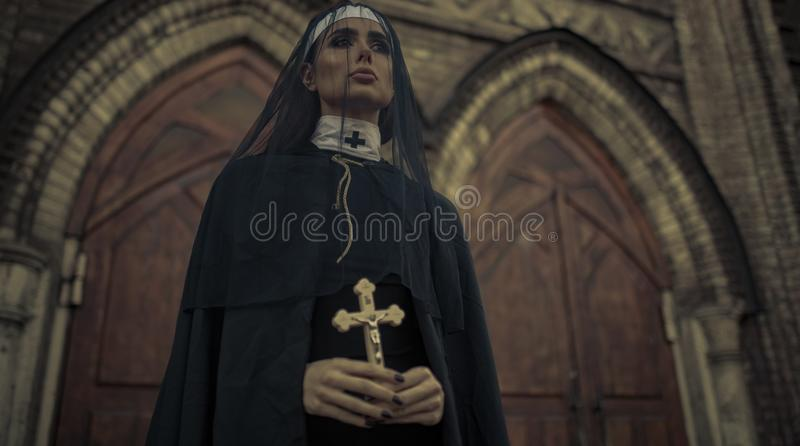 Młoda magdalenka jest stojąca i ono modli się z krzyżem w jej rękach na tem zdjęcie stock