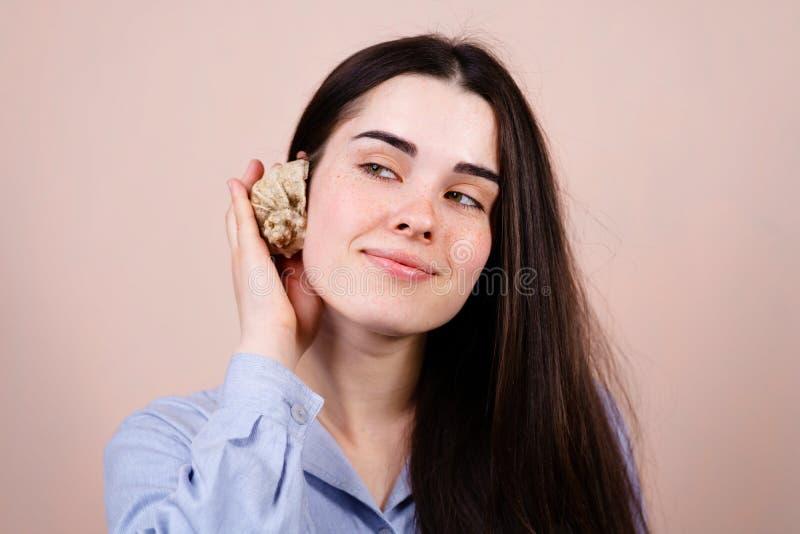 Młoda marzycielska uśmiechnięta kobieta słucha skorupa zdjęcie royalty free