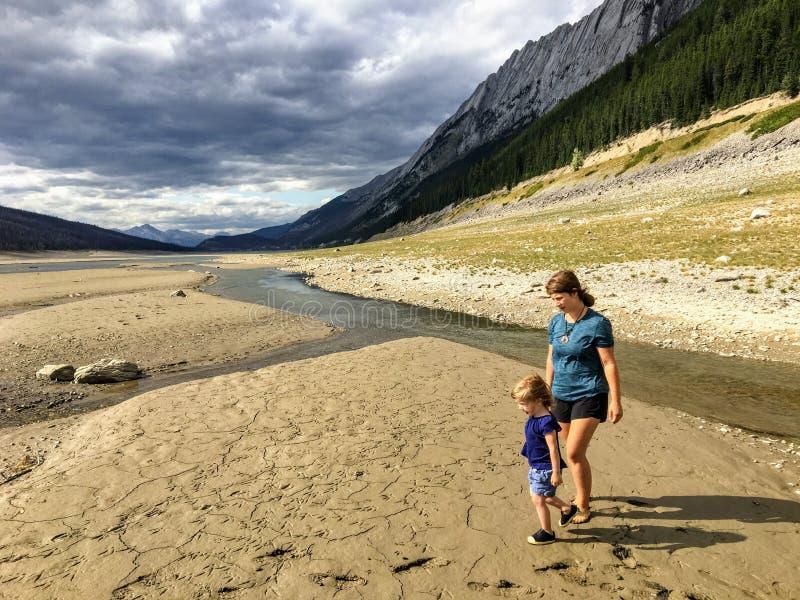 Młoda matka i jej mała dziewczynka bada wysuszonego - za jeziornym łóżku medycyny jezioro fotografia stock