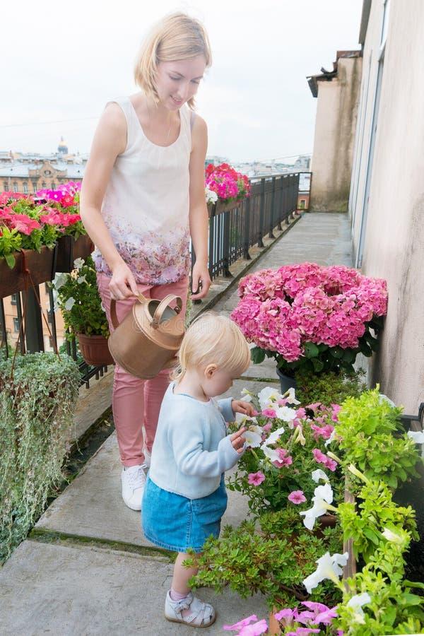 Młoda matka z dziewczyną z małego malucha podlewająca kwiaty zdjęcie stock