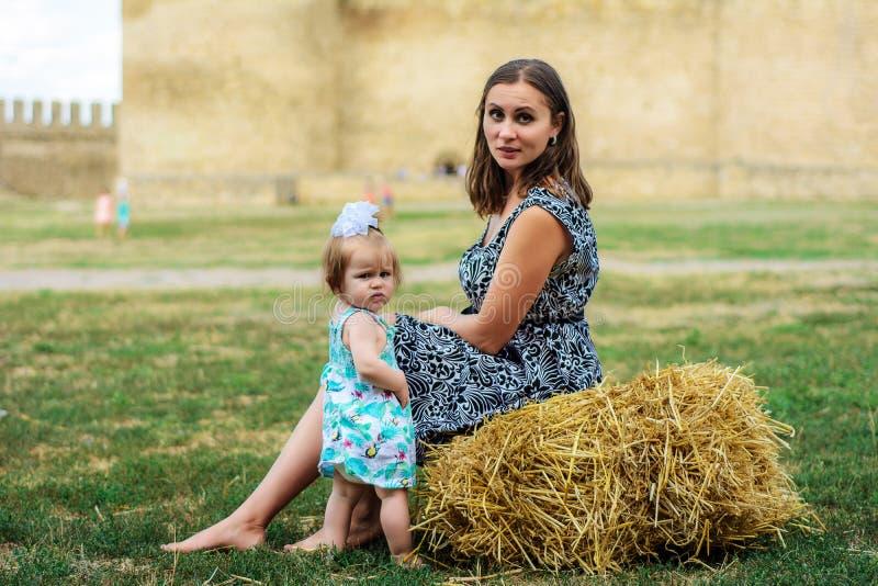 Młoda matka z jej córką siedzi na słomie blisko fortecy obraz stock
