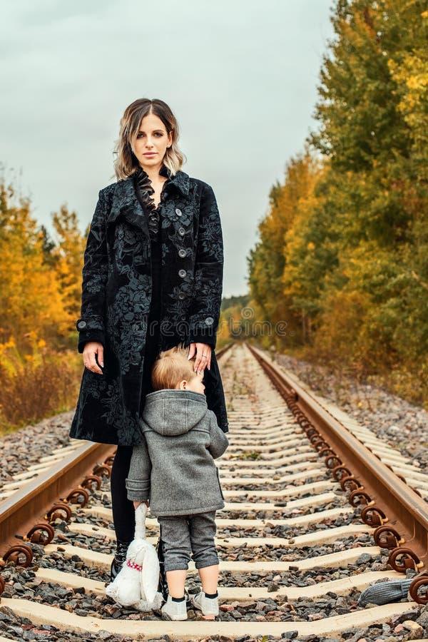 Młoda matka z małym synem na poręczach w lesie przed burzą fotografia stock