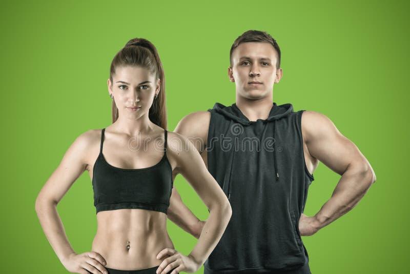 Młoda mięśniowa kobieta i dysponowany mężczyzny stojak na zielonym tle obraz royalty free