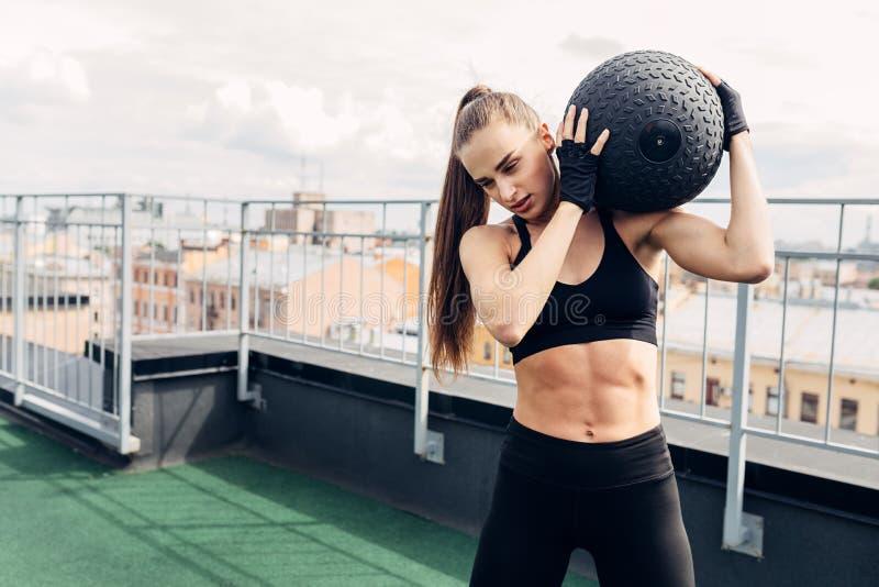 Młoda mięśniowa kobieta trzyma medycyny piłkę zdjęcia royalty free