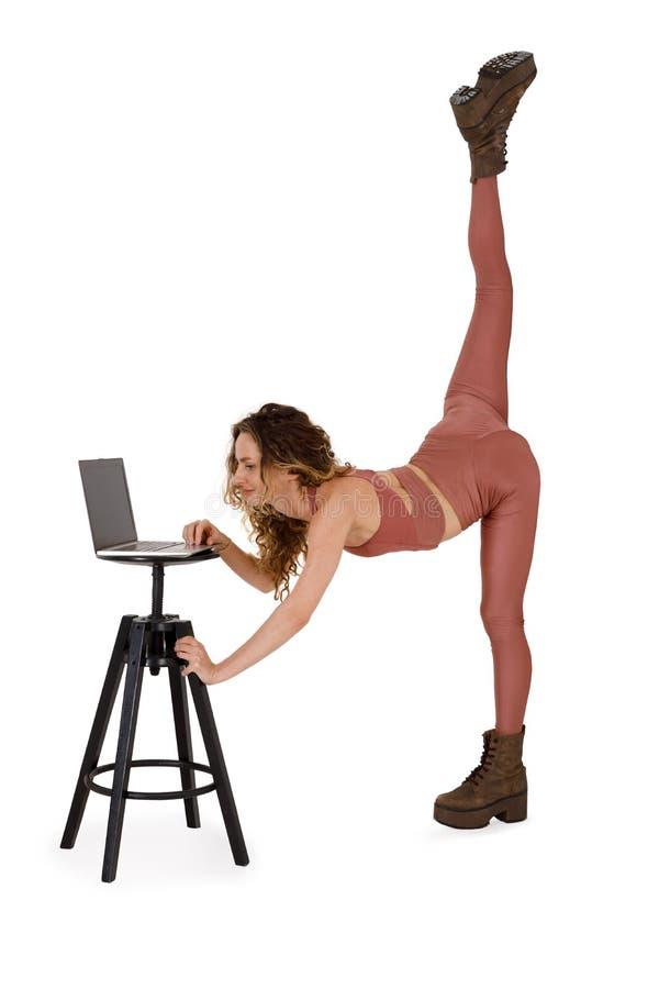 Młoda miła kobieta pracuje na laptopie stojącym na jednej nodze obrazy stock
