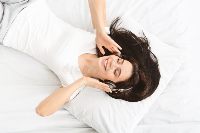 Młoda millennial kobieta słucha muzyka w łóżku zdjęcie royalty free