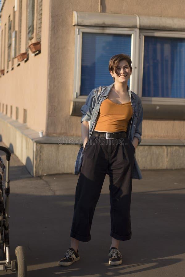 Młoda modna dziewczyna w pomarańczowym temacie, drelichowej koszula i szerokich spodnie stojakach blisko domu przy zmierzchem, obrazy royalty free