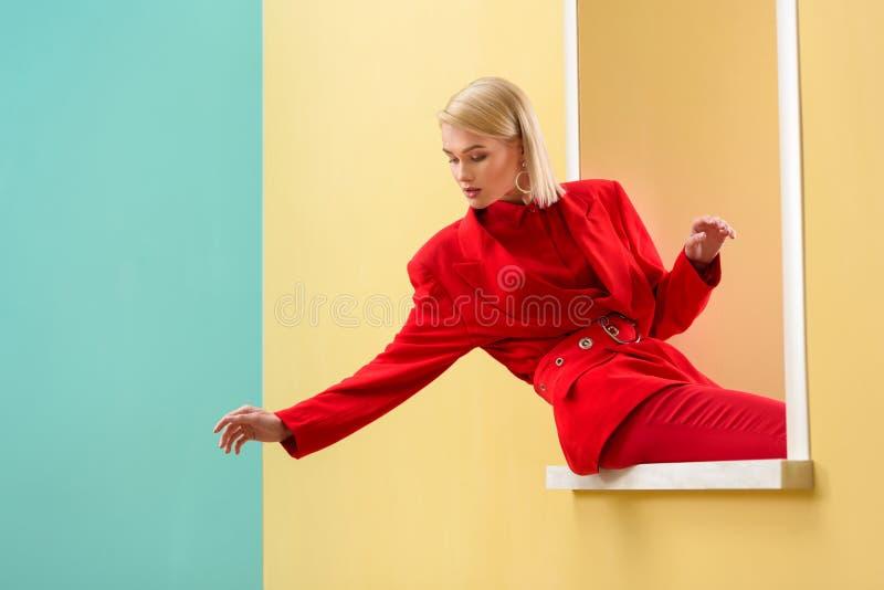 młoda modna kobieta w czerwonym kostiumu przyglądającym out zdjęcia stock