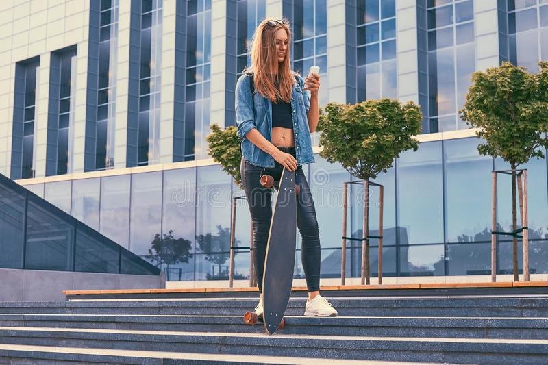 Młoda modniś blondynki dziewczyna w przypadkowych ubraniach, stoi na krokach przeciw drapaczowi chmur, używać smartphone, odpoczy obrazy royalty free