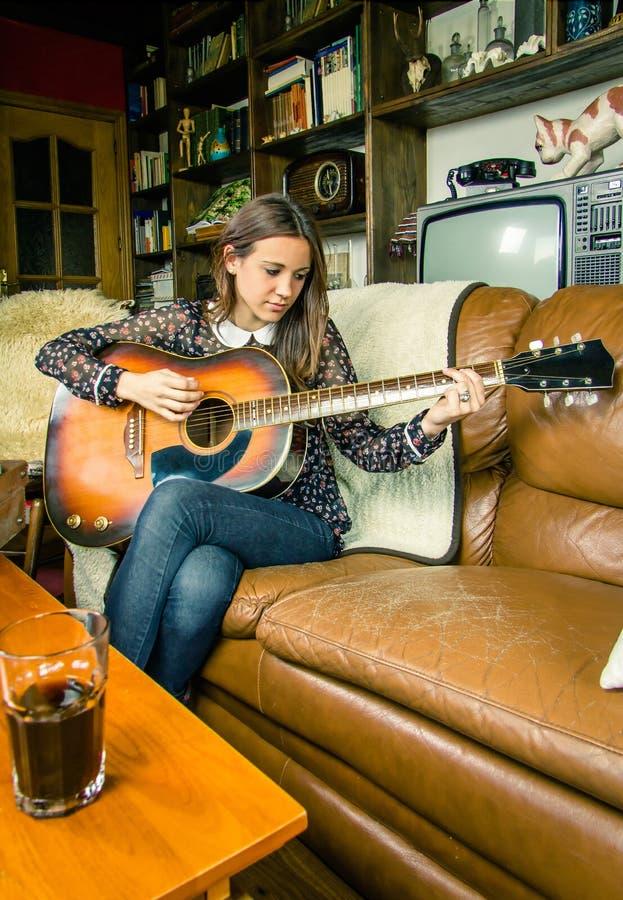 Młoda modniś dziewczyna bawić się gitarę akustyczną w domu zdjęcia royalty free