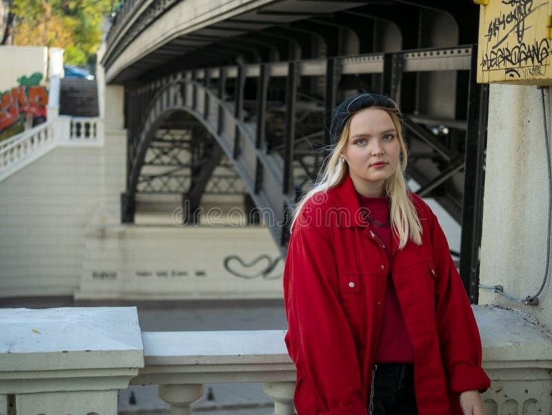 Młoda modniś dziewczyny blondynka w trykotowego czarnego kapeluszu i kurtki czerwonych stojakach pod mostem zdjęcia stock
