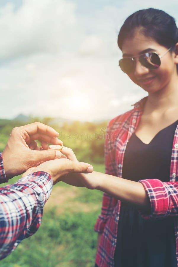 Młoda modniś para jest ubranym pierścionek zaręczynowego w naturze, cukierki i obraz royalty free