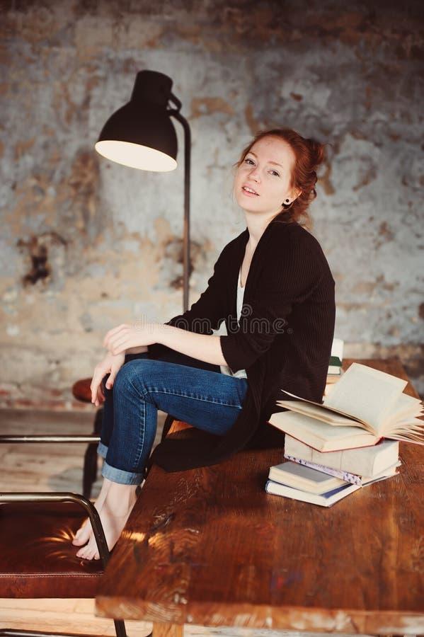 Młoda modniś rudzielec kobieta relaksuje w domu, siedzący na drewnianym stole z książkami fotografia royalty free