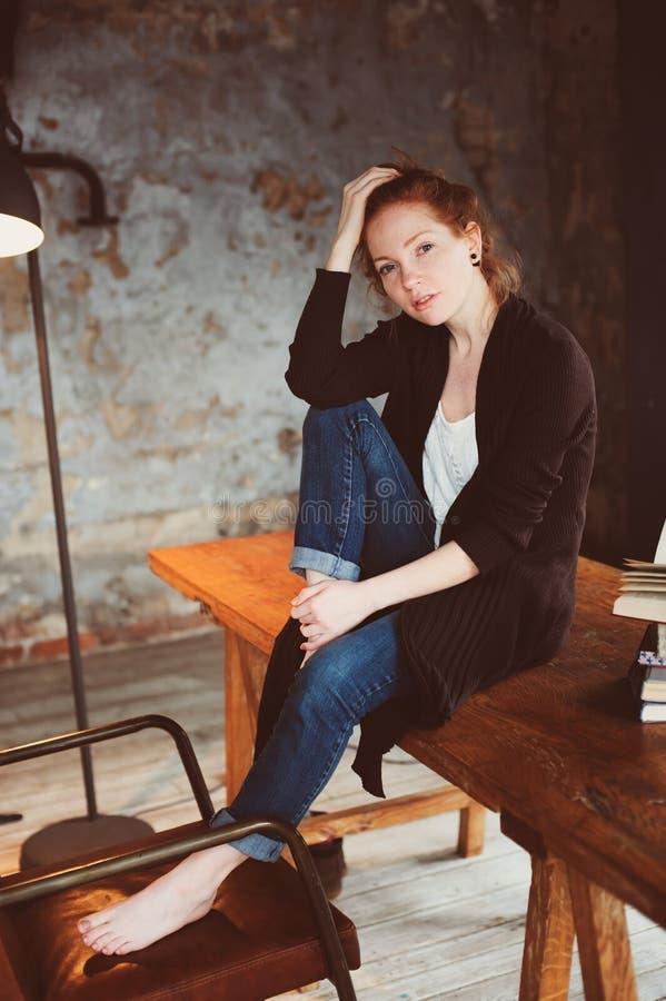 Młoda modniś rudzielec kobieta relaksuje w domu, siedzący na drewnianym stole z książkami zdjęcia stock