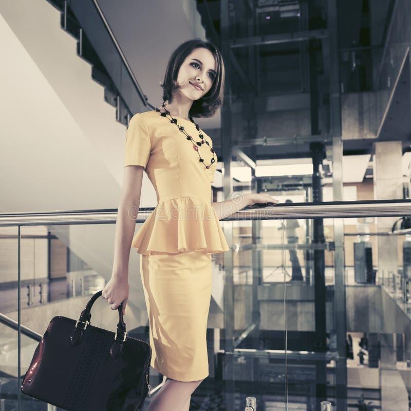 Młoda mody biznesowa kobieta w żółtej peplum sukni z torebką przy biurem obrazy royalty free