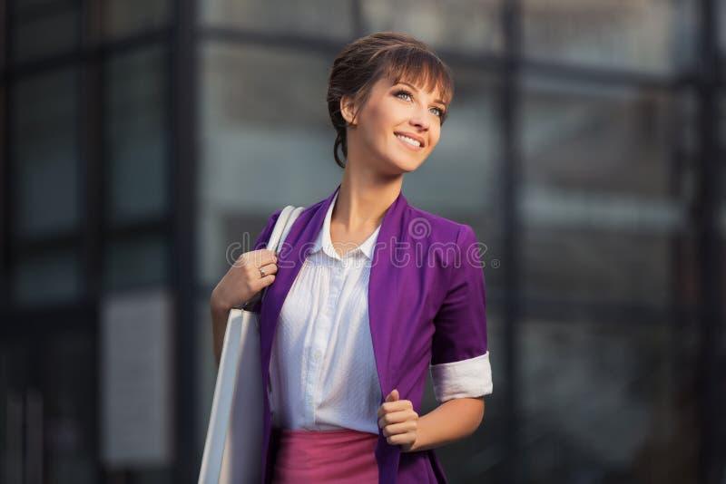 Młoda mody biznesowa kobieta w purpurowym blezerze z torebki odprowadzeniem przy centrum handlowym fotografia royalty free