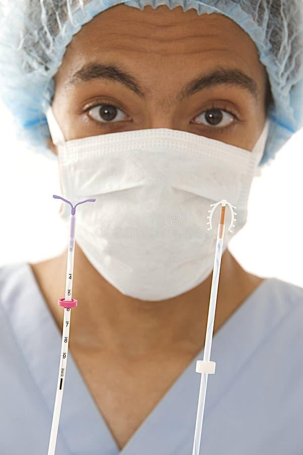 Młoda mulat lekarka trzyma dwa typ IUD kontrola urodzin groszaka zwitki przyrząda w jego rękach zdjęcia royalty free