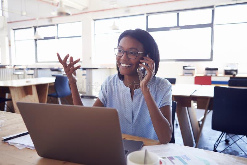 Młoda murzynka na telefonie przy pracą w officeï ¿ ½ zdjęcia royalty free